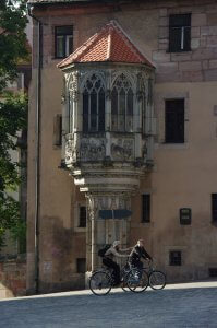 image of cyclists on cheap bikes riding hill past a building of gothic architecture