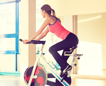 Young, Athletic women in pink riding spin bike in privacy