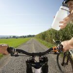 Image of A lady on mountain bike handing her friend a bottle of water while cycling.