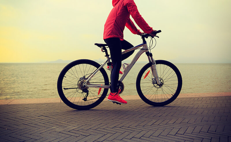 image of lady riding bike near ocean