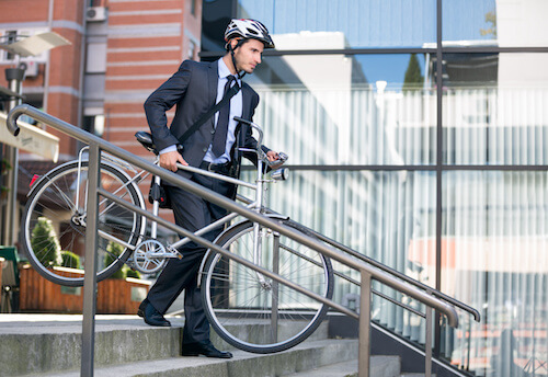 cyclist in helmet and suit carries road bike
