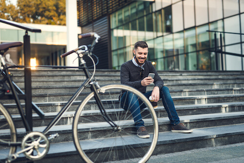 image of hipster surfing phone next to hybrid bike
