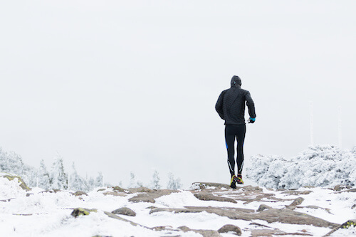 runner in black warm sportswear running in wind and fog on the high mountain trail in the winter