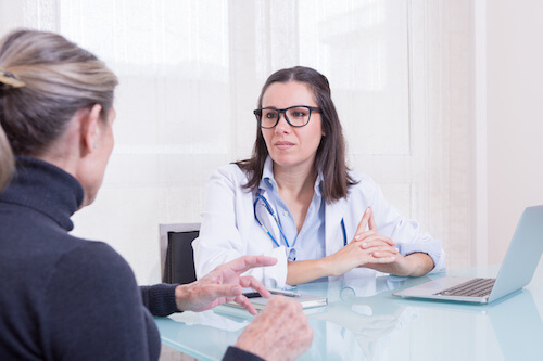 female patient talking to female doctor in consulting room.