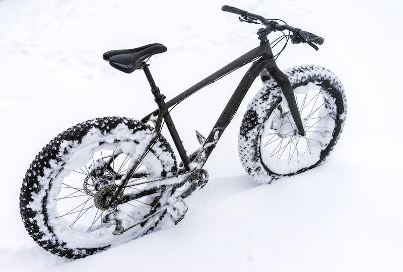 A picture of a fat tire bicycle in heavy snow.