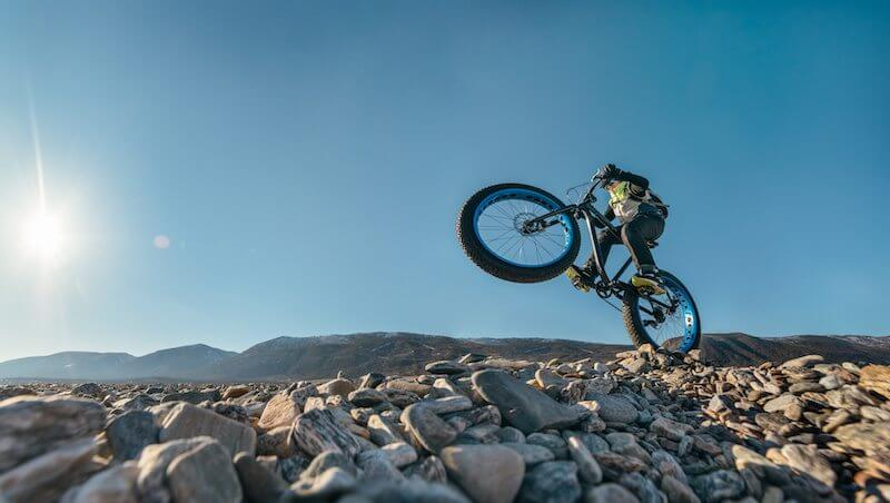 raveller athlete jumps on the bike on the rocky shore of Lake Baikal, with mountain views.