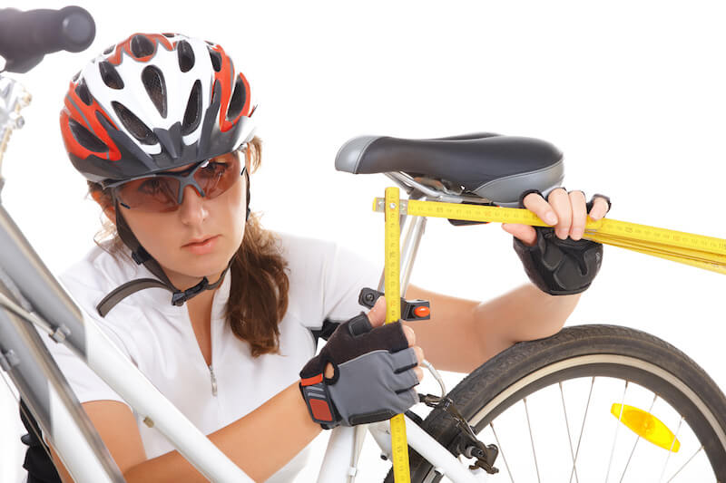 image of lady cyclist Measuring and making an adjustment in the bike saddle