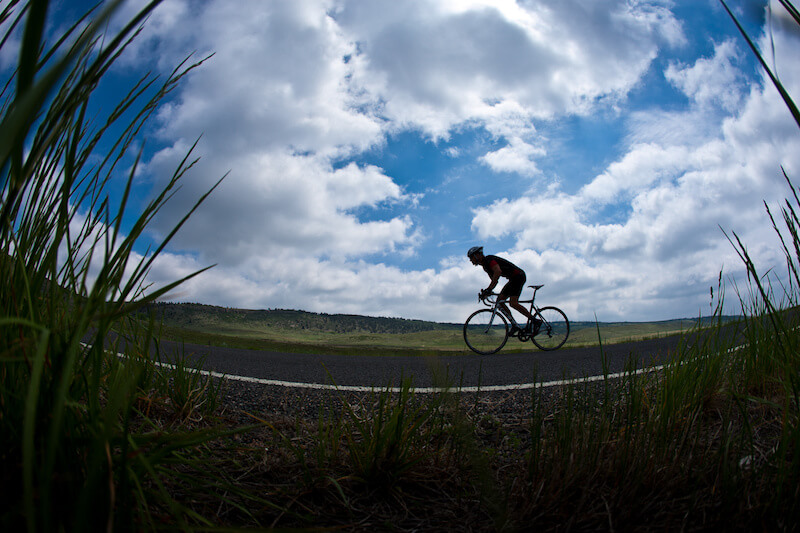 image of man riding bike on road with sky above him