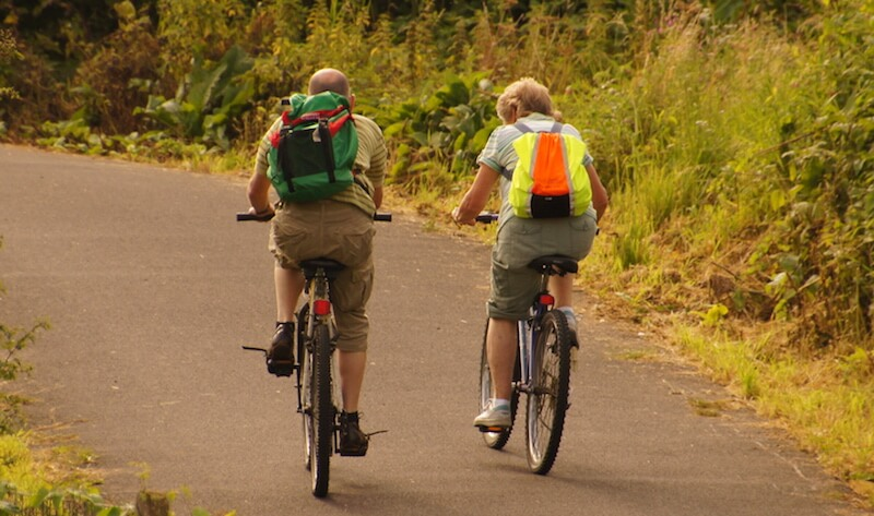image of two men riding a bike path wearing camelbaks