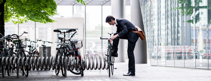image of businessman rolling down his pants legs after riding to work - best commuter bike