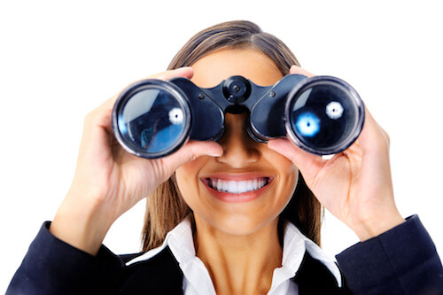 image of woman looking at reader through binoculars and smiling