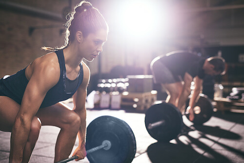 man and woman lifting weights in gritty gym