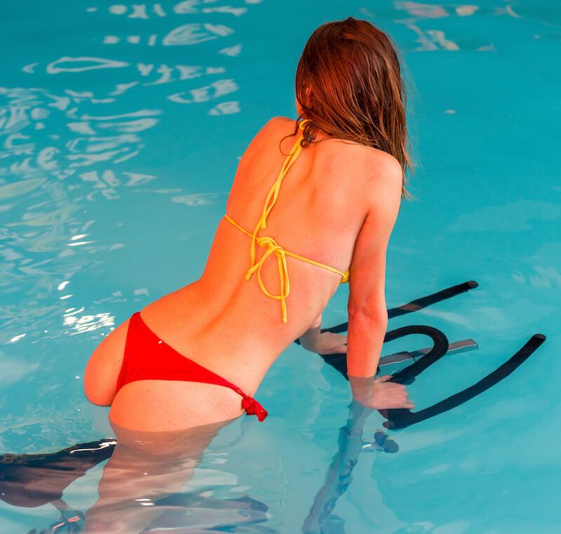 girl in bikini on spin bike in water