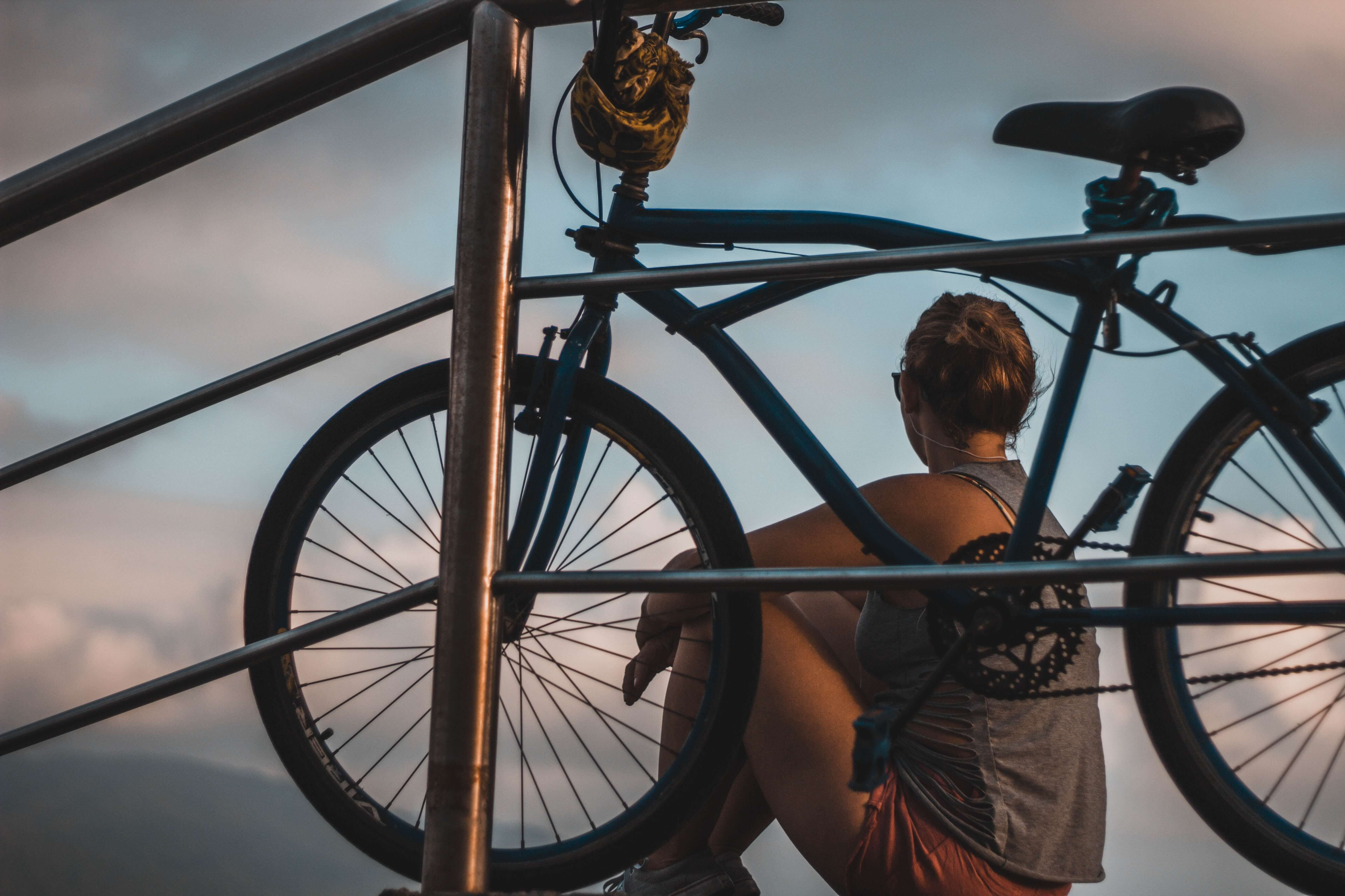 woman sitting next to a bike looking out into the clouds