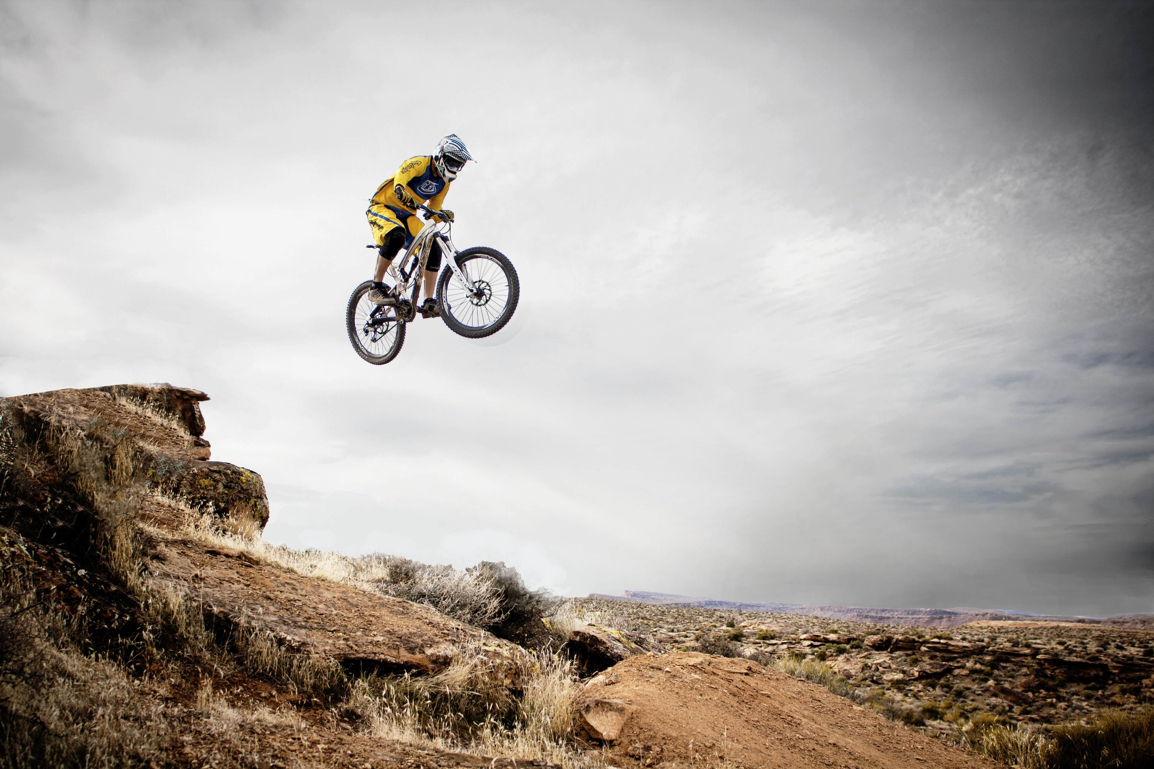 Action bicyclist jumping a rocky mound