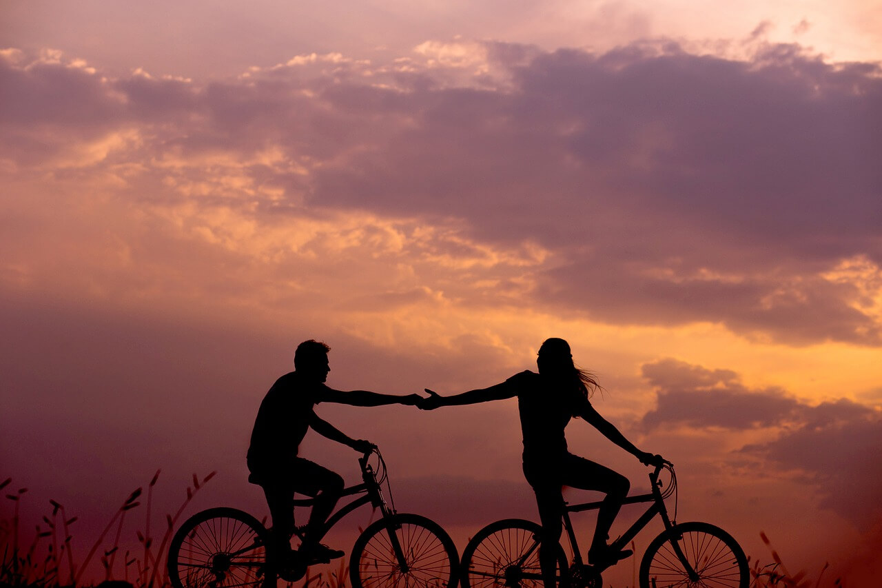 Silohuette of a couple on bikes reaching out to hold hands