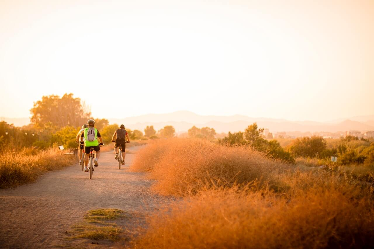 Orange sunset with bicyclists on a dirt road