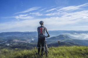 biker holding mountain bike on top of mountain