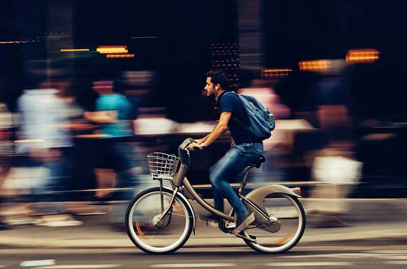person riding a bike on a city block