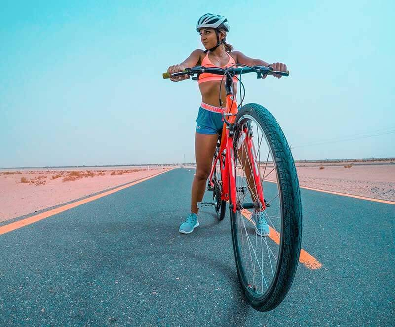 A fit woman sitting on her red bicycle