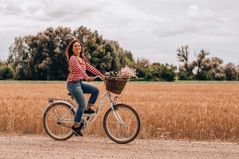 woman biking down a dirt road