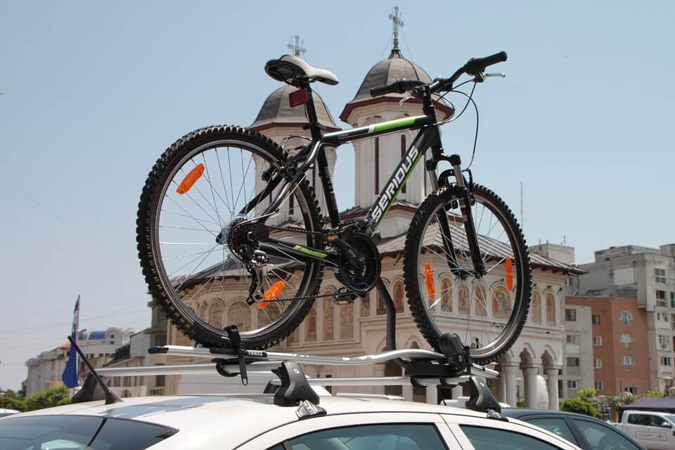 bicycle placed on the roof of the car with a bike carrier