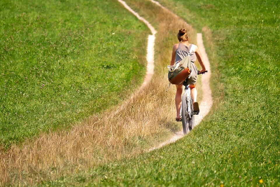 Cyclist wearing a sling bag is paddling the mountain bike at the green field