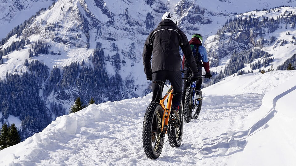 2 men is paddling the Mountain bikes on the snow