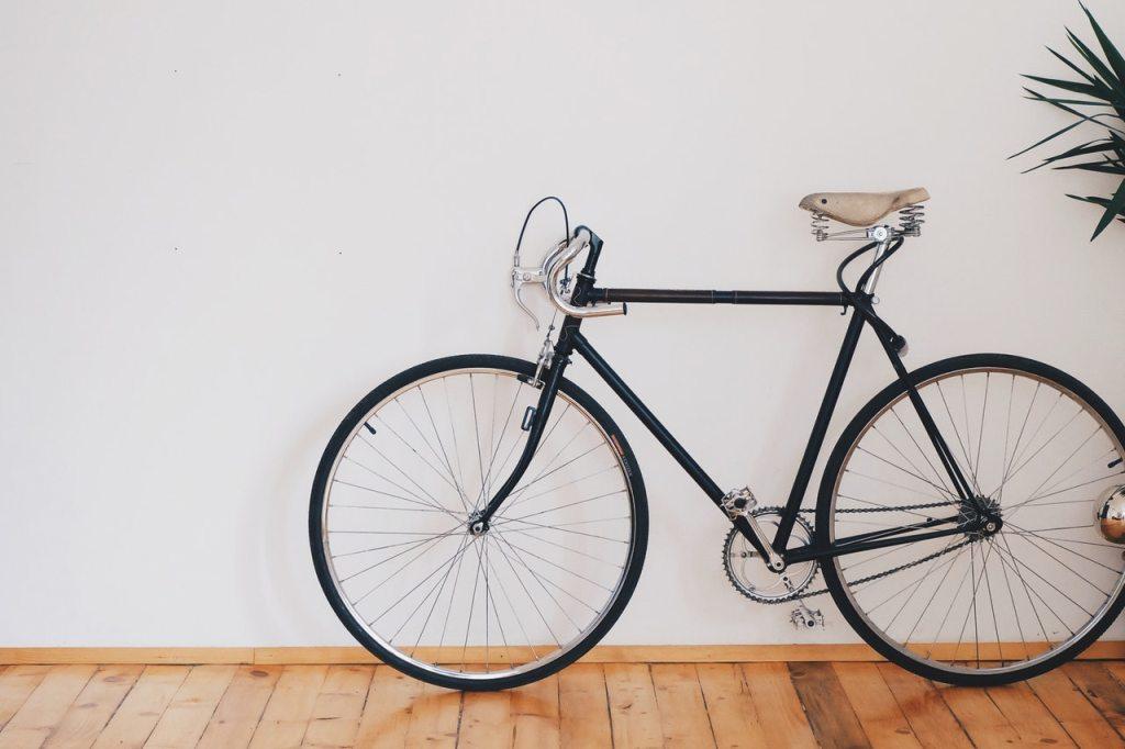 black road bike leaning against a wall