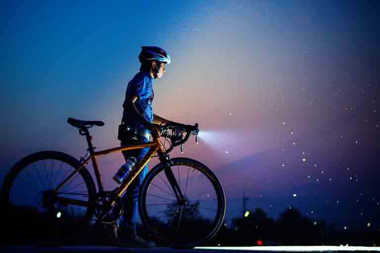 a man holding his bike with accessories like the water bottle and bike lights