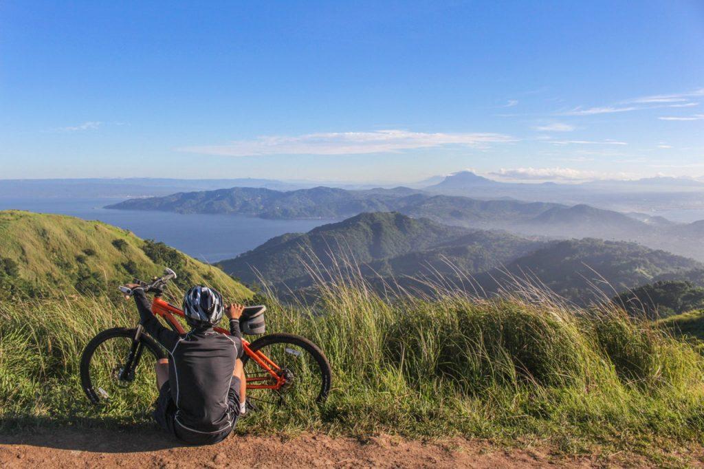 Man sitting beside bicycle
