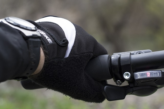 close-up photo focused on the left hand of a cyclist wearing bike gloves