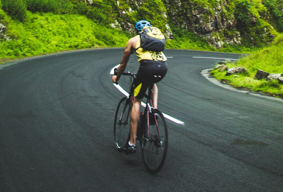the benefits of cycling being enjoyed by a man in cycling gear with backpack on a winding mountain road going down hill