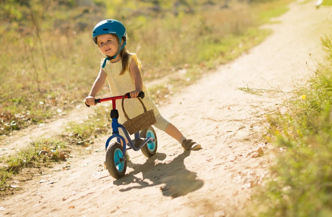 girl on bike on a gravel path with a helmet and basket