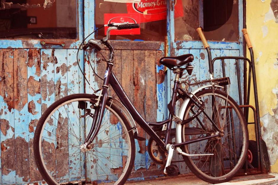 old bicycle leaning against a wall, abandoned