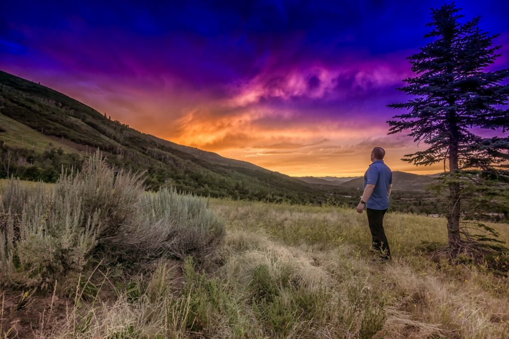 A man with his back to the camera looks at a sunset in Park City, Utah, one of our great destinations to bike